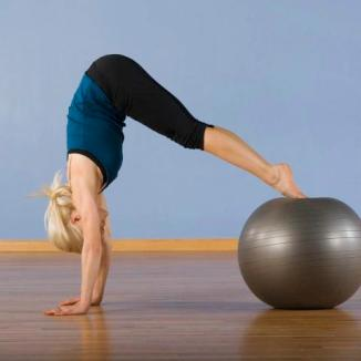 Woman exercising with ball --- Image by © Erik Isakson/Tetra Images/Corbis